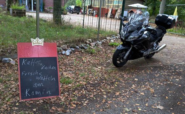essen auf raedern im winter: motorrad vor werbeschild fuer kaffee und kuchen am kamin