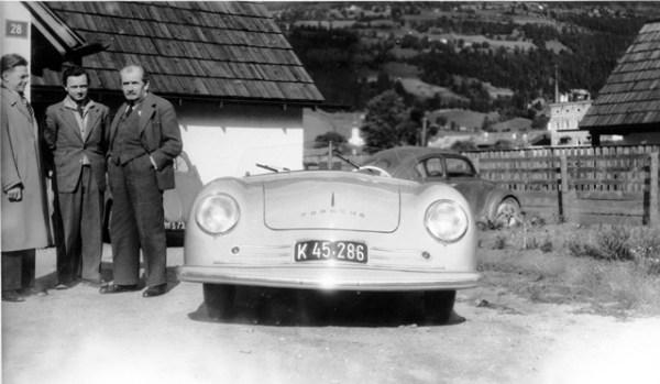 """Ferdinand Porsche (derecha), su hijo Ferry (al centro) y un caballero sin identificar posan junto al primer auto en llevar el nombre """"Porsche"""". Esta semana se cumplen 66 años del lanzamiento de ese primer Porsche, el 356. Noten al fondo de la foto el par de Volkys primitivos con ventanas traseras divididas o """"split window"""". FOTOS: Porsche"""