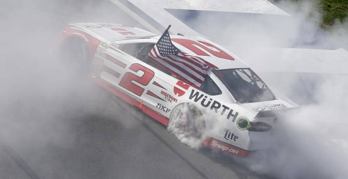 Brad Keselowski celebrates with a traditional burnout after winning the Auto Club 400.