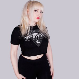 Pale skinned, alternative model with platinum blonde hair, red lipsticks and winged eyeliner wearing black crop top with Motowitch Collective Triangle logo on the front.