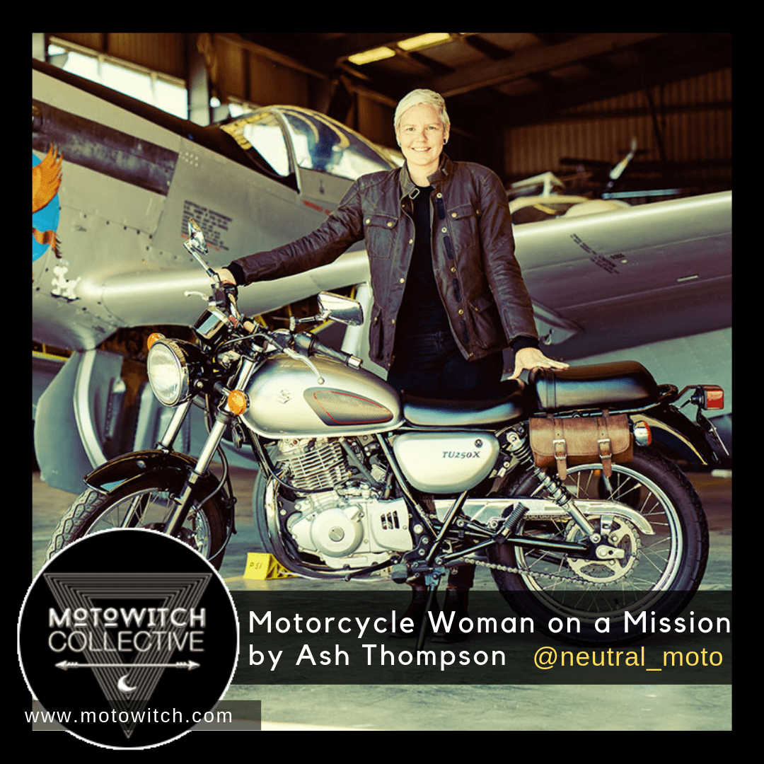 smiling woman with short platinum blond hair standing next to her susuki motorcycle in front of a propeller airplane
