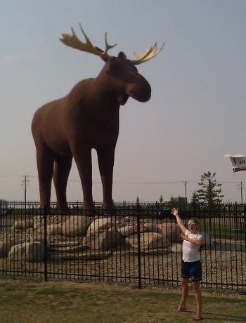 girl gesturing at giant statue of moose with a small jet plane visible in background, mounted in an action pose