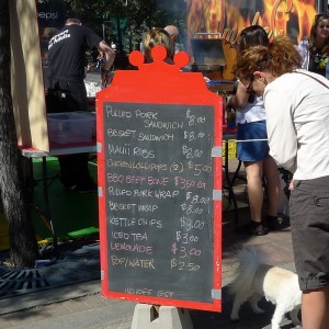 Red-framed blackboard with BBQ menu, a lady and a small white dog beside it