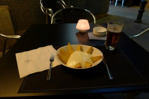A black table set for one with a glass of beer and a bowl of potato wedges covered in a white sauce