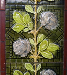 Glazed ceramic tile featuring a straight stalk with green leaves and purple flowers like roses branching off the sides, all on a dark green background