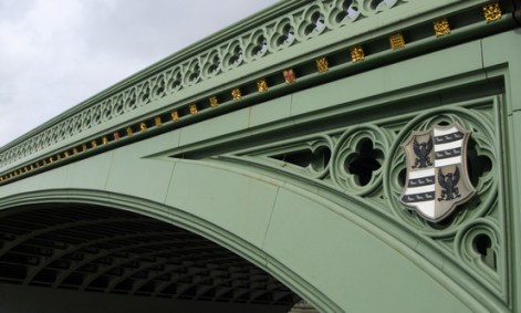Green arch of a bridge with gold crests and a black and white coat of arms