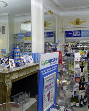 Merchandise in a variety store beside a marble fireplace, large mirror, luxurious look