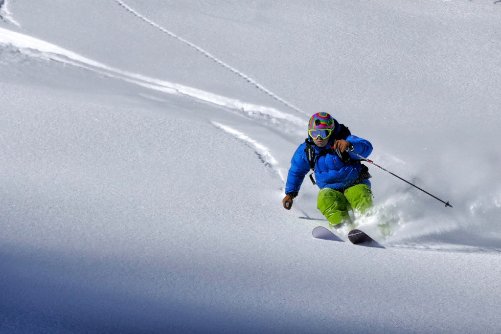 A man skiing downhill, a source of common skiing injuries.