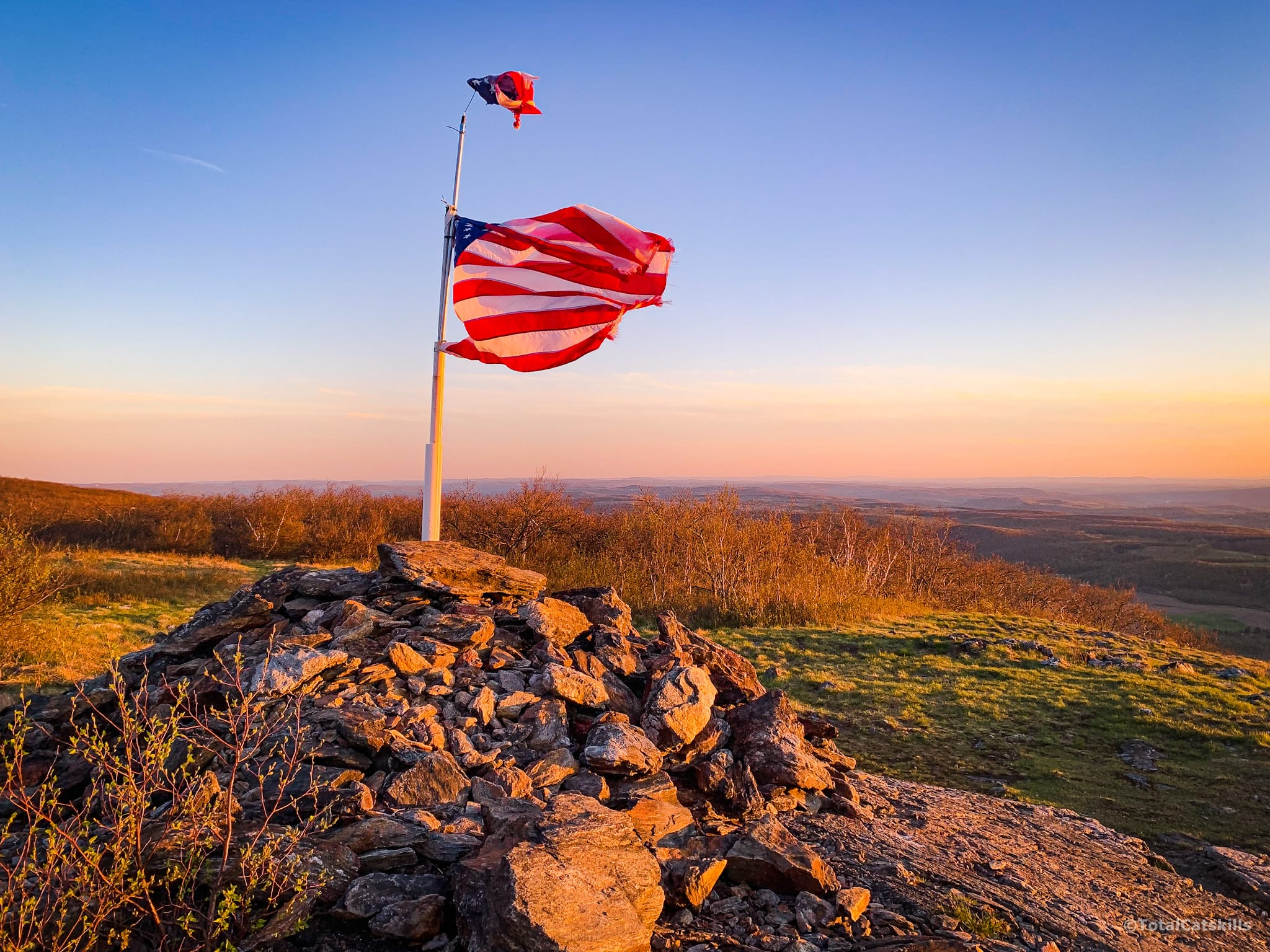 american flag on mountain summit at sunset