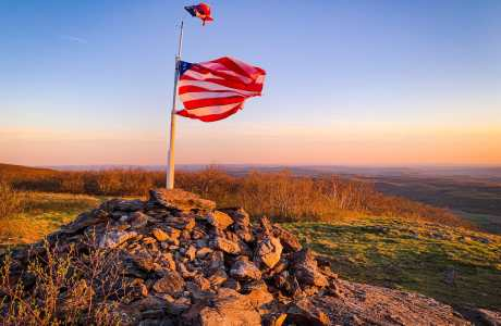 american flag on mountain summit at sunset
