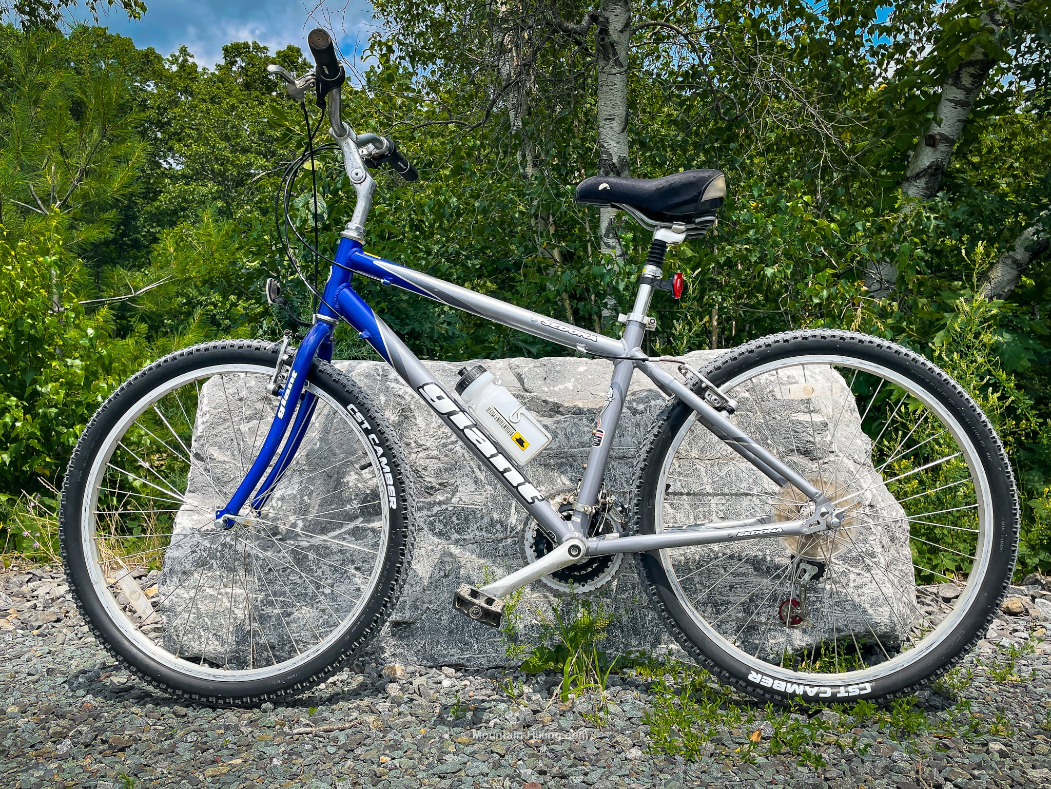 blue and silver mountain bike leaning against boulder