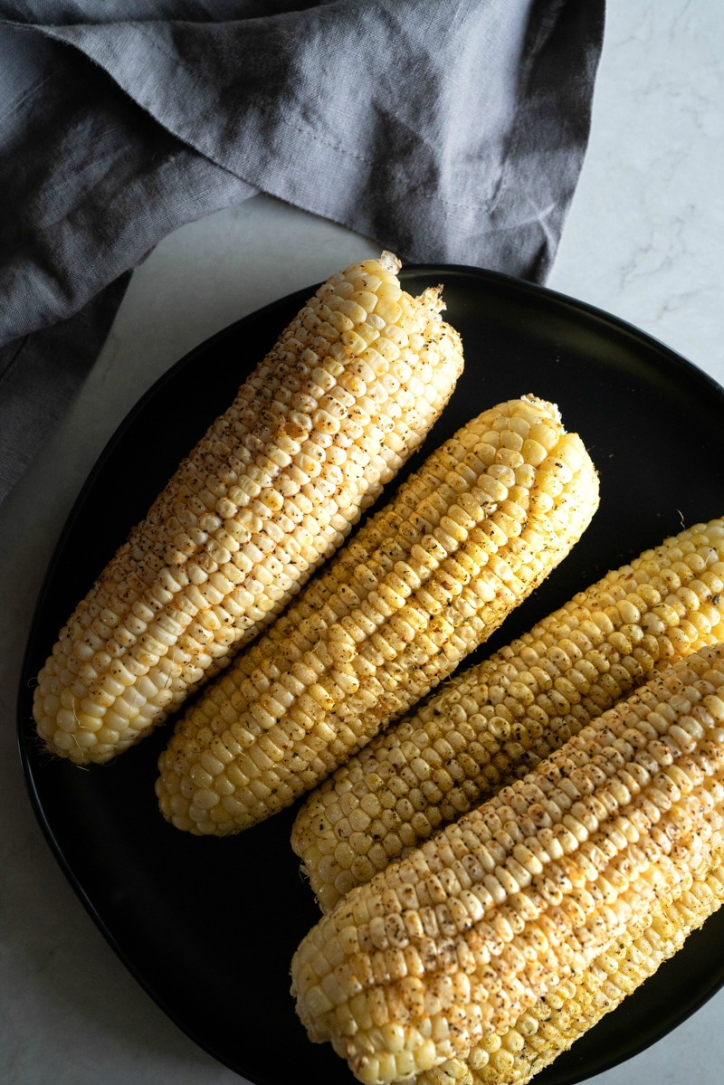 A plate of corn on the cob that has been roasted on the grill