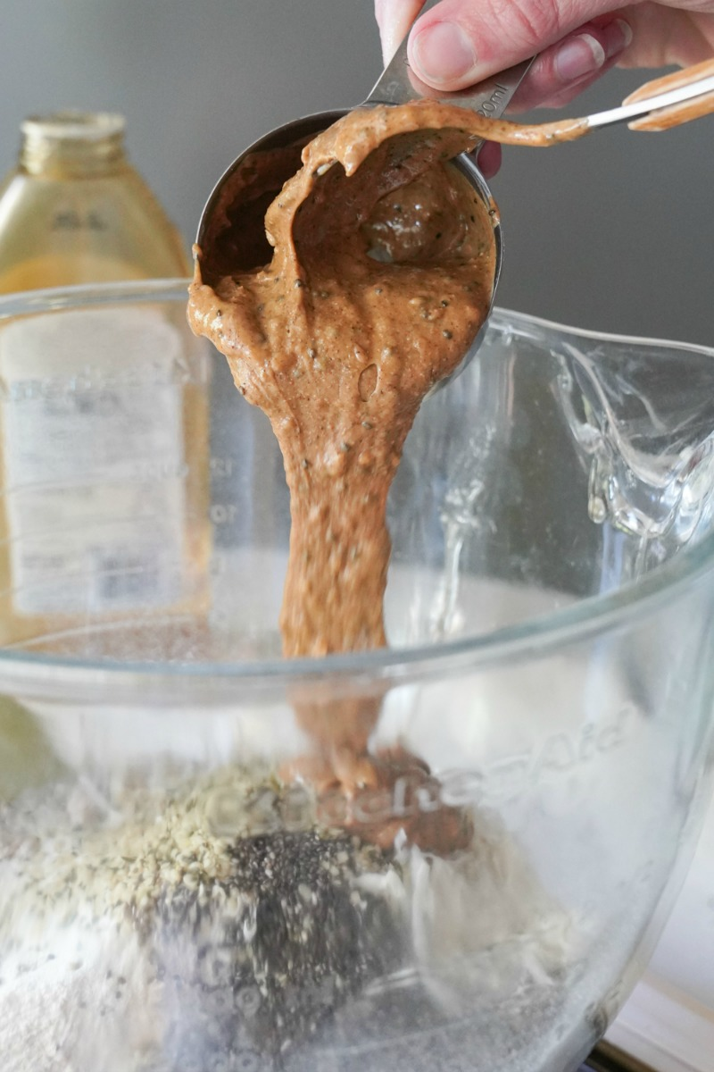 A close up of pouring my favorite nut butter from Costco into a kitchen aid mixer. Making a recipe for protein balls