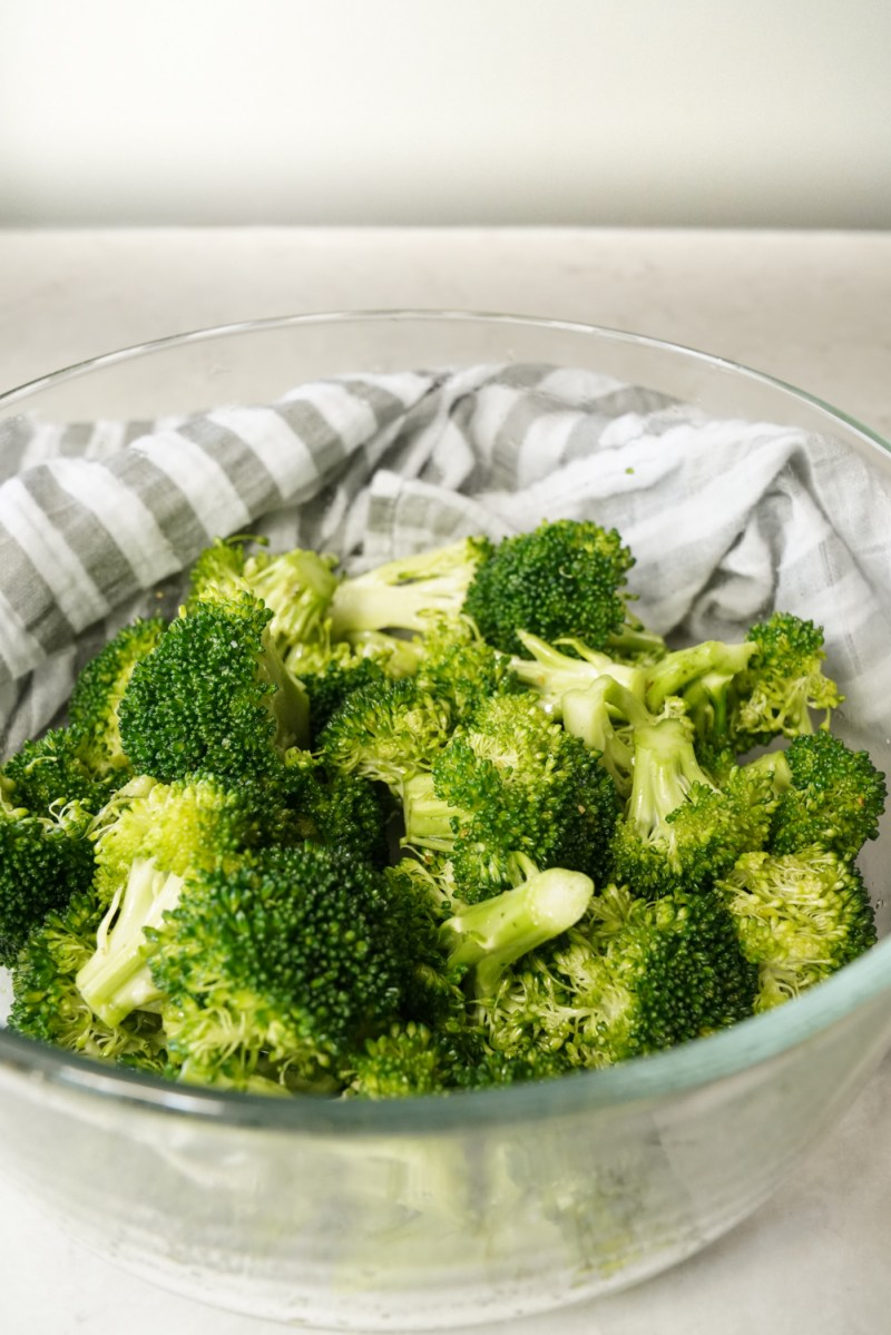 A bowl of broccoli prepped for a sheet pan stir fry. Simply seasoned with olive oil, salt and pepper.