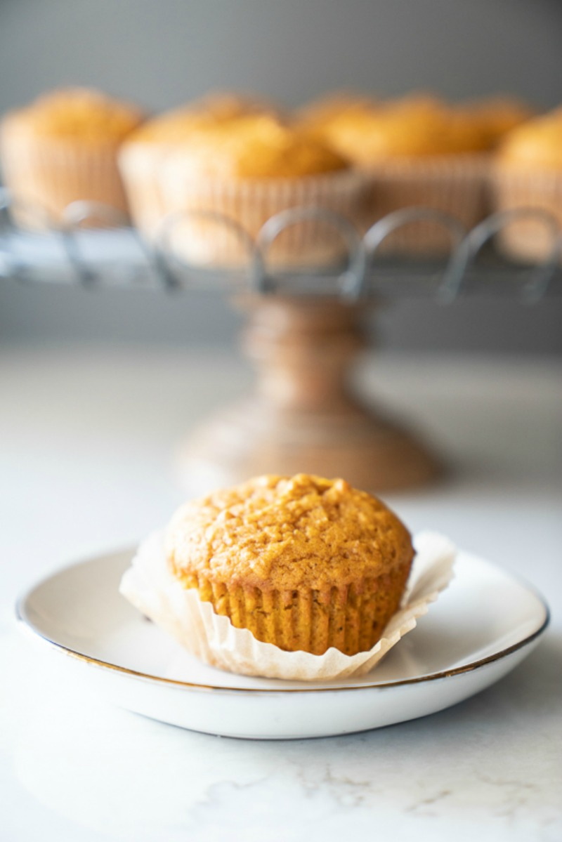 One pumpkin muffin is in focus while the stand behind is softly out of focus. www.mountainmamacooks.com