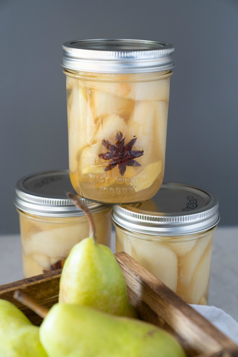 Three jars of canned pears. Highlighting the star anise in the jars. A brown basket filled with pears. www.mountainmamacooks.com