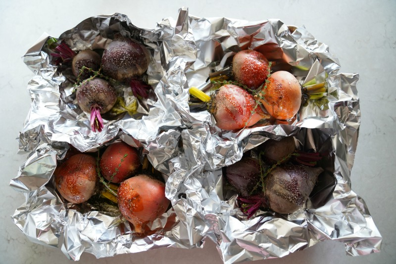 Four individual foil packets filled with beets. The beets are about to be roasted in the oven.  Recipe for pickled beets on www.mountainmamacooks.com
