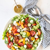 A bright and colorful salad with arugula, tomatoes, peaches, cucumber, mozzarella, and a balsamic vinaigrette. www.mountainmamacooks.com
