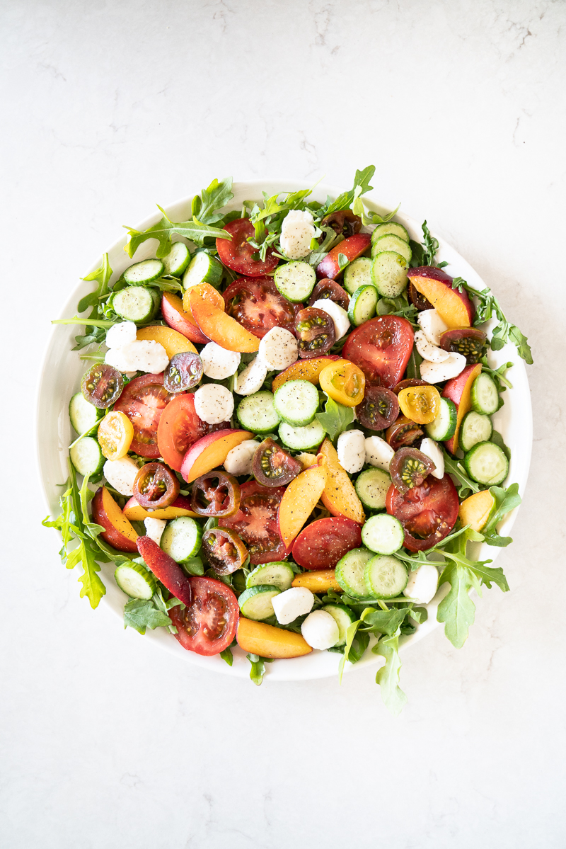 A gorgeous salad with arugula, peaches, mozzarella, cucumbers and a basil-balsamic vinaigrette. www.mountainmamacooks.com