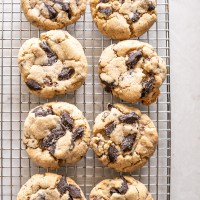A perfectly chewy peanut butter cookie studded with dark chocolate chunks and rolled in coarse sugar. Eight perfect cookies cooling on a baking rack. www.mountainmamacooks.com