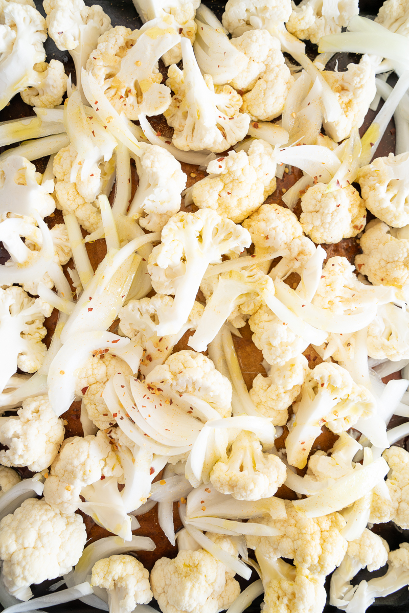 A full sheet pan full of raw cauliflower about to be roasted. A sheet pan full of roasted cauliflower with parmesan cheese. A small plate full of golden crusted cauliflower florets. Simply delicious recipe! www.mountainmamacooks.com