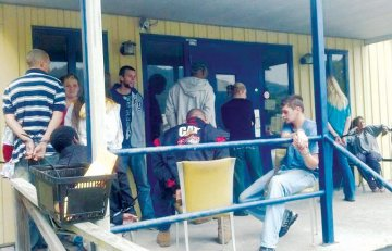 Handcuffed to porch railings are a few of the dozens arrested in Hinton for drug-related charges
