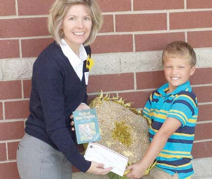 "Townley Hamilton, conservation chair of Lewisburg House and Garden Club congratulates second grader Joe Cochran on his 57"" sunflower, all around school winning entry in the Annual Sunflower Contest. She presented him with a book on the Birds of West Virginia' and a $25 check for his achievement."