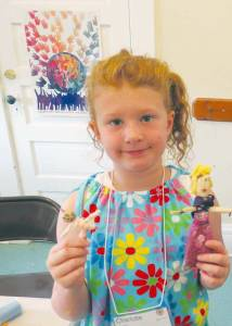 Kids' College Students Charlotte shows the dolls she made using corn husks, pipe cleaners and other craft supplies