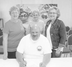 Seated: Mayor Copenhaver signs Community of Unity Day Proclamation. Standing: Organizers of Community of Unity Day events: Carol Ayers (left), Mary Ellen Reece and Lee Ann Grimes