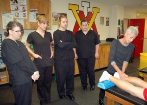"""Gloria Lawrence (far right), head of the Massage Therapy program at Dabney S. Lancaster Community College, demonstrates proper techniques to several of the students in her fall course during a clinical session in the Department of Sports Medicine at the Virginia Military Institute in Lexington. """"At VMI, cadets are treated in accordance with Orthopedic massage protocol to address deactivation of trigger points, reduction of adaptive load (biochemical, biomechanical) and/or enhancement of lymphatic and venous drainage to restore range of motion and enhance athletic performance,"""" says Lawrence. """"During the Spring 2015 semester, students will be continuing with clinical rotations at the Duke Cancer Center in Fishersville."""" Lawrence, who recently earned a national certification as a Natural Health Practitioner, has designed and developed the two-semester program to provide each student with experiential off-campus clinics for the most expansive skill-set training. """"This program is uniquely different from all other programs offered in Virginia,"""" notes Lawrence. """"The U.S. Bureau of Labor Statistics continues to project a 20-23 percent demand. At DSLCC we are committed to changing lives by changing futures, one student at a time."""" Students looking on are, from left: Doris Balser of Clifton Forge, AdriAnne Reyns of Covington, Cheyenne Adams of Buena Vista and Christa Thomas of Covington.  Clinicals for the College's program include hours at a wide variety of settings, such as retirement centers, hospitals, and sports-related venues, only a few of the many options for employment after completion of the program. For information regarding Fall 2015 enrollment, please contact Lawrence at 540-461-3447."""