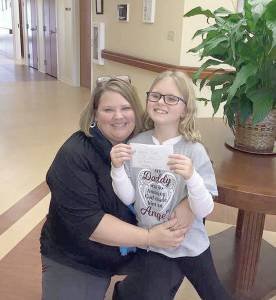 Local public relations and marketing coordinator Missy VanBuren welcomes Kaylee Pippin to the hospice facility in Fairlea. Pippin not only raised $800 in her father's name for the care center, but inspired a local golf course to raise much more.