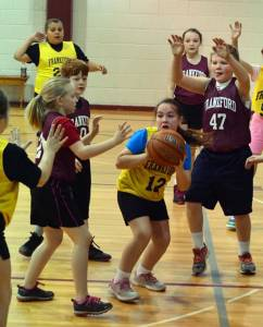 Alyssa Carpenter, #12, looks for a teammate, as Natalie Wellman, #2, and Hunter Cooper, #47, hope to grab the basketball. Alyssa's Pistons played the Falcons at Frankford, Saturday morning, Jan. 2, in the 3rd/4th grade division of rec league basketball. (Photo by Mark Robinson)