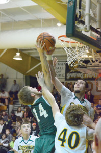 Evan Canterbury, #45, of the Greenbrier East Spartans floats high around the rim to block a shot by Jordan Richardson, #14, of the Hampshire Trojans in a game played in Fairlea Saturday evening, Jan. 30. The Trojans won the game, 62-56. (Photo by Mark Robinson)