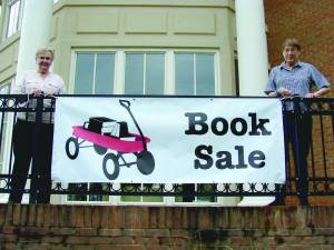 Greenbrier County Public Library Book Discussion Group members Julia Ford (left) and Jane Spicer preview book sale banner.