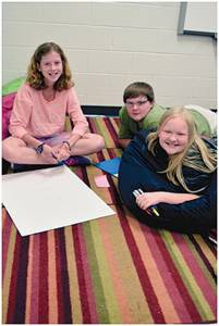 Laura Meadows, Colten Reeder and Paige Neff work on their branding for their presentation.