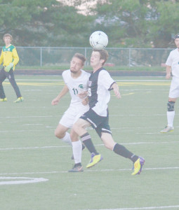 Doug McClung (left) playing defense for Greenbrier East's soccer team, runs in step with James Monroe's Kendale Meadows during a game played at Spartan Field Tuesday evening. East won, 5-0. (Mark Robinson photo)