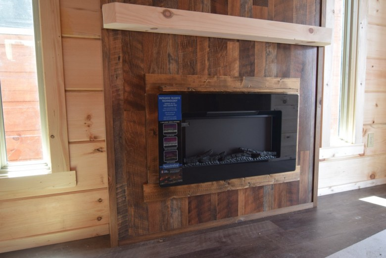 Electric wall fireplace shown with Barnwood surround