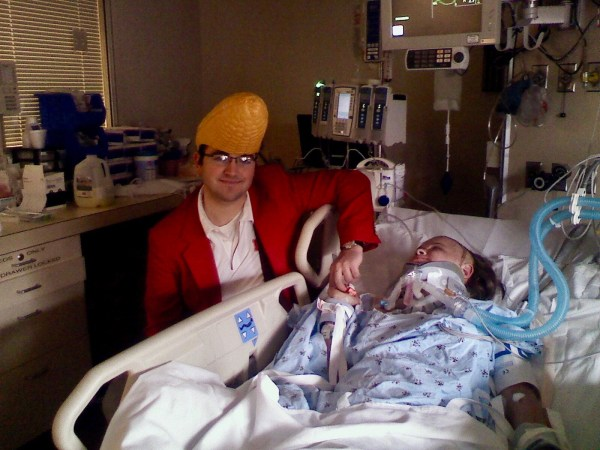 Ashley Stevens of Mountains Unmoved watching Gator Bowl 2009 from hospital room with fiancé in corncob hat
