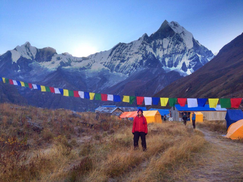 A hiker stands under prayer flags at Annapurna Base Camp