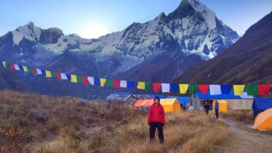 A hiker stands under prayer flags at Annapurna Base Camp