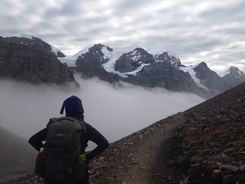 A solo female trekker in Nepal looking out to the cloud covered mountains.