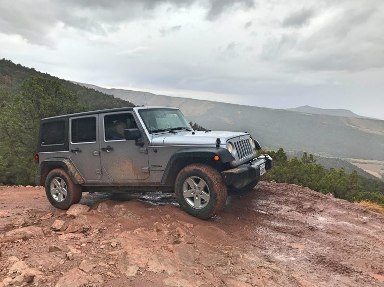 A silver Jeep on a muddy dirt road in the mountains.