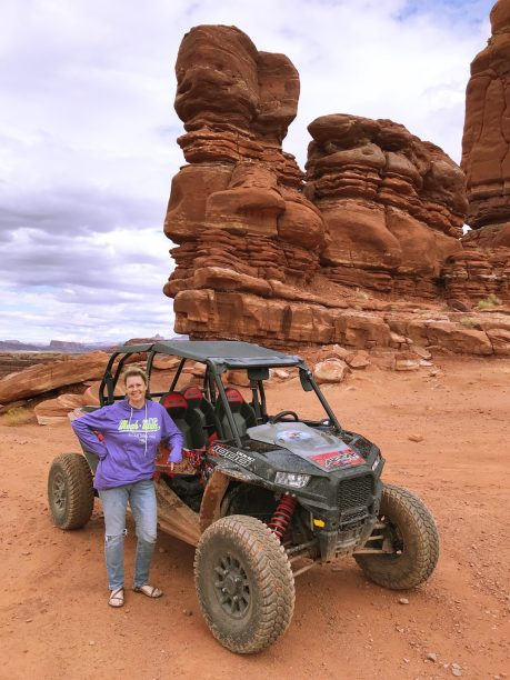 Mom in front of a side-by-side and towers of red rocks in Moab, Utah