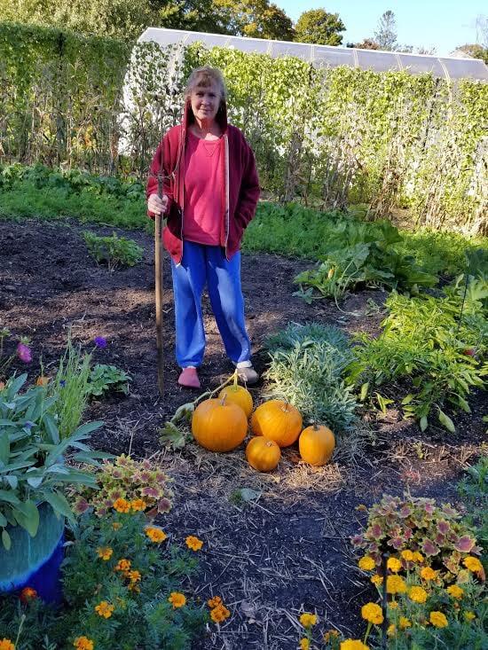 Woman standing in a garden with pumpkins