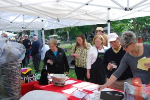 Association member and picnic co-organizer Sarah Hopkins (in apron) reviews the auction bids with other guests