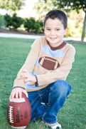 Mycah plays the game of fall with a brown and blue striped knit sweater with a football emblem by Hartstrings and Gap Denim blue jeans. Outfit provided by Angels & Rascals.