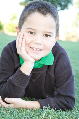 Mycah wears a green colored shirt and layers it with a dark gray knit sweater. Outfit provided by The Oops! Co.