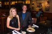 Jewel Davey, property accountant for Mount Pleasant Towne Centre wears a knee length Jessica Howard dress with black sequins and satin ruffle hem while enjoying a calamari appetizer with her co-worker, Andy Lowe, at Carrabba's in Mount Pleasant. Andy, general manager for Mount Pleasant Towne Centre, wears gray, Calvin Klein suit separates from the Modern Fit Collection. Styling and make-up provided by Belk in Mount Pleasant Towne Centre.