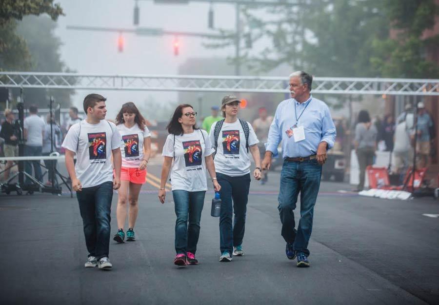 Julian Smith walking with race volunteers at the Asheville Half Marathon.