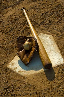 A Baseball, glove and bat laying on home plate